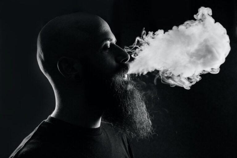 mężczyzna z brodą palący papierosa